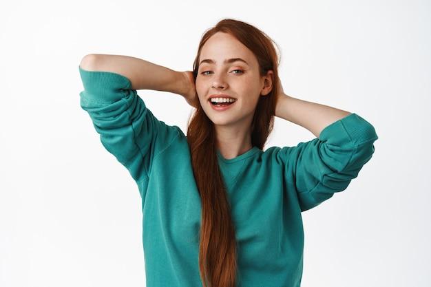 Fröhliches, ungestörtes ingwermädchen, das sich ausruht und die sommerferien genießt, die hände hinter dem kopf hält, lügt und entspannt, lächelt zufrieden auf weiß.