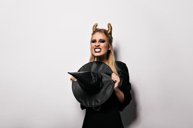 Fröhliches vampirmädchen, das in halloween aufwirft. emotionale junge hexe, die party genießt.