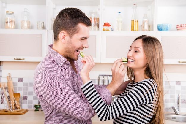 Fröhliches verliebtes paar, das sich gegenseitig mit gurke füttert