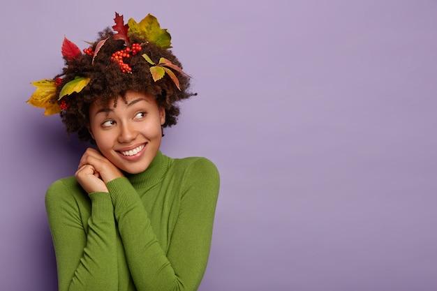Fröhliches, verträumtes afroamerikanisches mädchen neigt den kopf, lächelt angenehm, schaut zur seite, macht ein porträt im innenbereich, hat gelbe blätter, ebereschenbeeren im haar