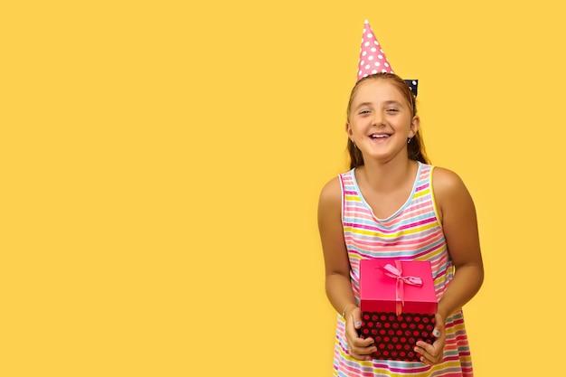 Fröhliches weibliches kind, das schreit und geschenkbox hält, ist aufgeregt und überrascht, geburtstagsgeschenk zu bekommen, auf gelbem hintergrund