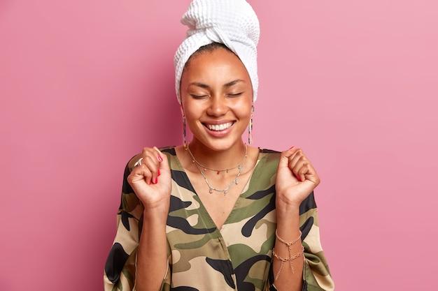 Fröhliches weibliches model hält die fäuste geballt lächelt aufrichtig hält die augen geschlossen hat gesunde haut in häuslicher kleidung gekleidet hat ein handtuch auf dem kopf gewickelt genießt es, zeit zu hause zu verbringen posen drinnen
