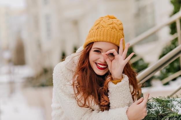 Fröhliches weibliches modell, das spaß im winter hat. erfreute kaukasische ingwerfrau, die über natur lacht.