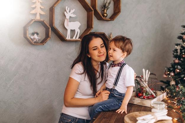 Fröhliches weihnachtsporträt der glücklichen mutter und des glücklichen sohnes mit neujahrsgeschenken und heiligabend mit feierdekoration und weihnachtslichtern