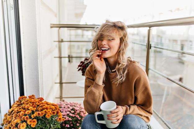 Fröhliches weißes mädchen, das tee am balkon genießt. prächtige junge frau, die an der terrasse kühlt.