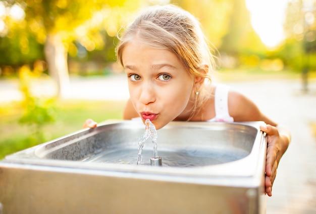 Fröhliches wundervolles mädchen trinkt kühles frisches wasser von einem kleinen brunnen in einem sommerwarmen sonnigen park während eines lang erwarteten urlaubs