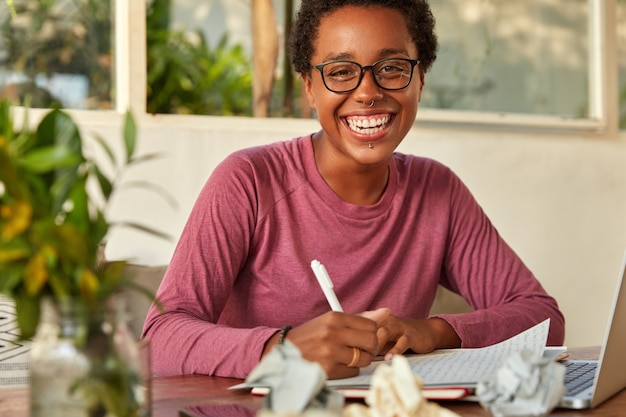 Froh, dass positive dunkelhäutige junge frau einige informationen von der webseite auf ein leeres blatt papier umschreibt