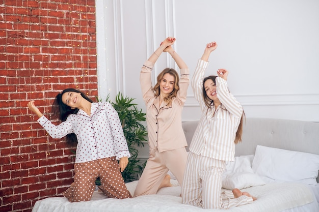 Froh. drei junge mädchen haben eine pyjama-party und fühlen sich fröhlich