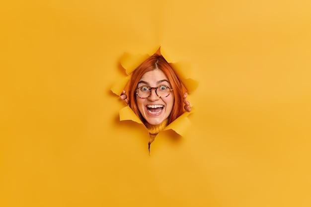 Froh erstaunt erstaunt rothaarige kaukasische frau schaut mit breitem lächeln reagiert auf etwas sehr gutes trägt optische brille schaut durch papierloch