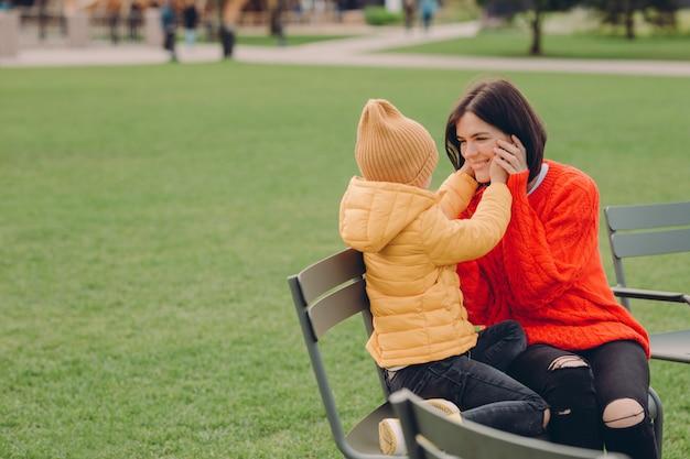 Froh, junge mutter und tochter sitzen im freien auf dem chiar, haben positive ausdrucksformen