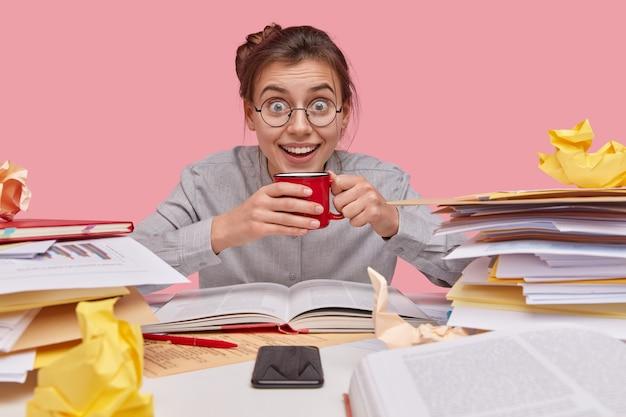 Froh lächelnder kaukasischer schüler mit entzücktem ausdruck, hält rote tasse, erledigt papierkram, trägt runde brillen, ist in hochstimmung