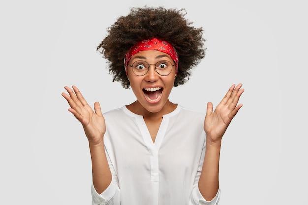 Froh überrascht, schöne junge afroamerikanerin gestikuliert aktiv und ruft laut aus, schockiert von niedrigem preis und verkauf, trägt stilvolles stirnband und bluse, isoliert über weißer wand.