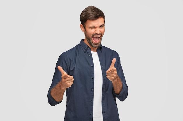 Froh, unrasierter mann blinzelt mit dem auge, öffnet mund und zeigt, fühlt sich aufgeregt, trägt freizeitkleidung, demonstriert seine wahl, steht an weißer wand. freudiger europäischer mann drinnen