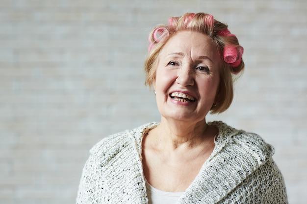 Frohe ältere frau mit haarlockenwicklern