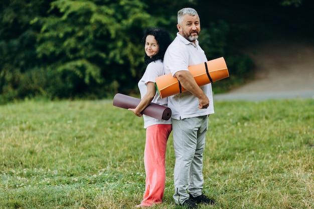 Frohe ältere frau und mann, die eine yogamatte und -c $ schauen hält. sport