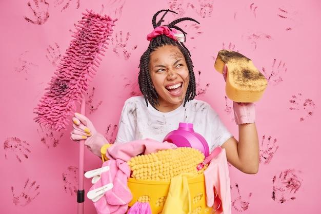 Frohe afro-amerikanerin wischt staub im schmutzigen raum ab, hält mopp und schwamm schaut glücklich weg, wäscht sich am wochenende gerne hat geflochtene frisur-posen mit schmutziger kleidung und gesicht gegen rosa wand
