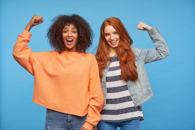 Frohe attraktive damen, die glücklich aussehen und fröhlich lachen, ihre hände heben und gleichzeitig starken bizeps demonstrieren, isoliert über der blauen wand