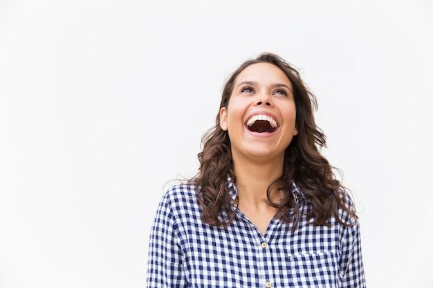 Frohe aufgeregte frau, die über witz lacht