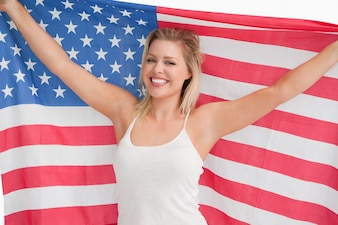 Frohe blonde Frau, welche die Sternenbanner Flagge hält