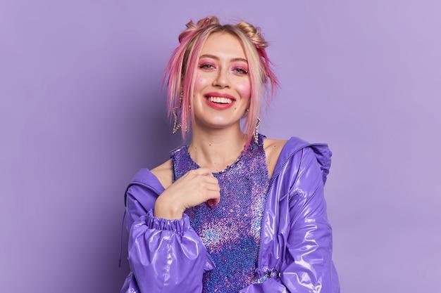 Frohe blonde schöne europäische frau mit hellem lebendigem make-up gekleidet in modischen kleidungsposen