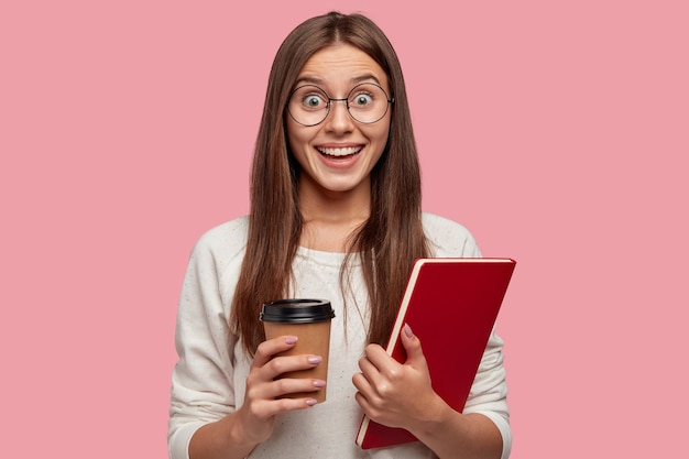 Frohe brünette frau mit aufgeregtem ausdruck, sieht glücklich aus, trägt eine runde brille, hält ein rotes lehrbuch und nimmt kaffee heraus, reagiert auf gute nachrichten von klassenkameradin, isoliert auf rosa wand