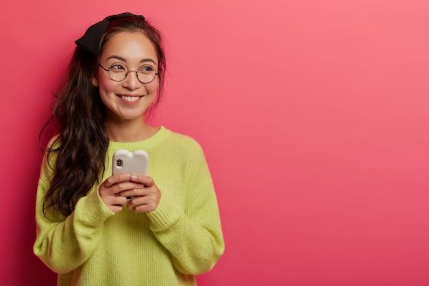 Frohe brünette frau surft im internet über das handy, macht online-shopping