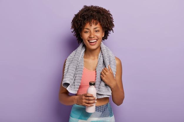 Frohe charmante fitnessfrau trinkt kaltes wasser, ist nach dem laufen durstig, hat handtuch am hals
