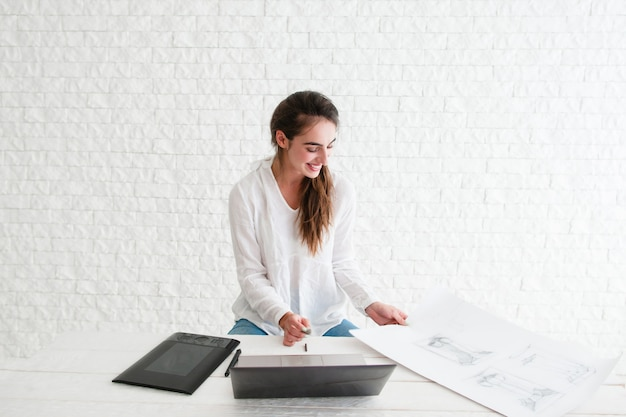 Frohe designer-retusche-skizze auf laptop