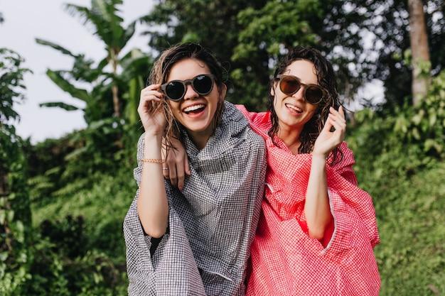 Frohe dunkelhaarige frauen mit sonnenbrille, die über die natur lachen. gut gelaunte weibliche touristen in regenmänteln, die spaß im dschungel haben.