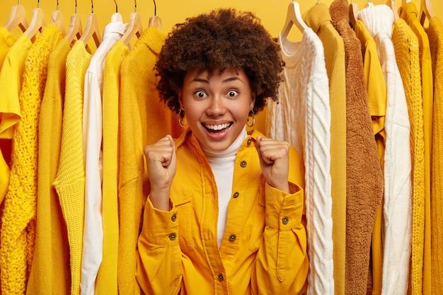 Frohe dunkelhäutige frau mit afro-frisur, geballten fäusten, in modische kleidung gekleidet, steht in der nähe von hängenden kleidern auf schienen