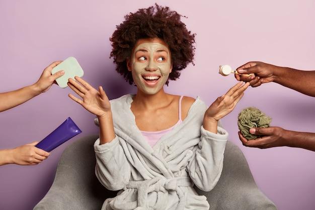 Frohe ethnische frau mit tonmaske, hebt handflächen, umgeben von händen einer kosmetikerin, im bademantel gekleidet, posiert im sessel