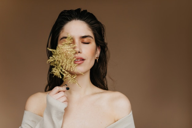 Frohe europäische dame mit nacktem make-up, das mit pflanze aufwirft. glamouröses brünettes weibliches modell, das kühlt.