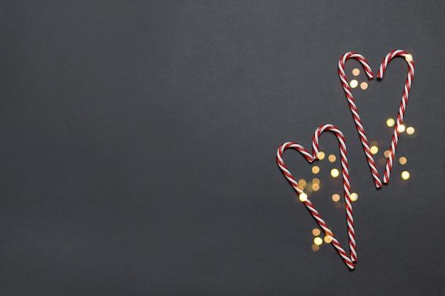 Frohe feiertage grußkarte mit zuckerstange in einer herzform mit einem funkeln auf dunkelheit