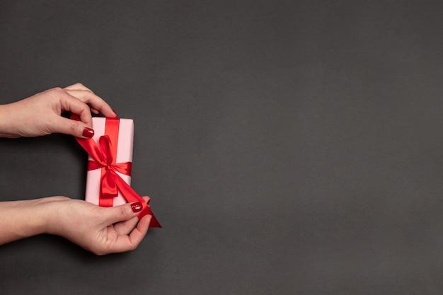 Frohe feiertage konzept mit den frauenhänden, die präsentkarton mit rotem bogen auf dunklem pastellhintergrund halten