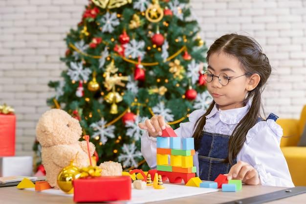 Frohe feiertage und frohe weihnachten kindermädchen, das zu hause spielwaren spielt.