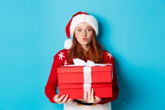 Frohe feiertage und weihnachtskonzept. nettes rothaariges mädchen, das geschenke und faltenlippen für kuss hält, weihnachtsmütze und lustigen pullover trägt, blauer hintergrund.