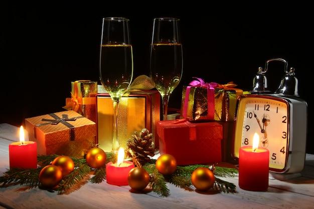 Frohe festtage dekoration mit weihnachtskugeln, geschenkboxen, uhr und kerzen.