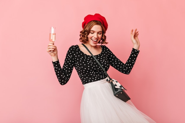 Frohe französische frau, die mit weinglas tanzt. studioaufnahme des glückseligen lockigen mädchens, das spaß auf rosa hintergrund hat.