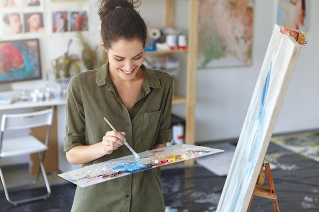 Frohe frau, die als malerin arbeitet, nahe staffelei steht, pinsel hält, abstraktes bild mit bunten ölen schafft, gute laune und inspiration hat. weibliche zeichnung auf leinwand. kunstkonzept