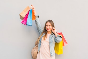 Frohe Frau, die mit hellen Einkaufstaschen an der hellen Wand steht