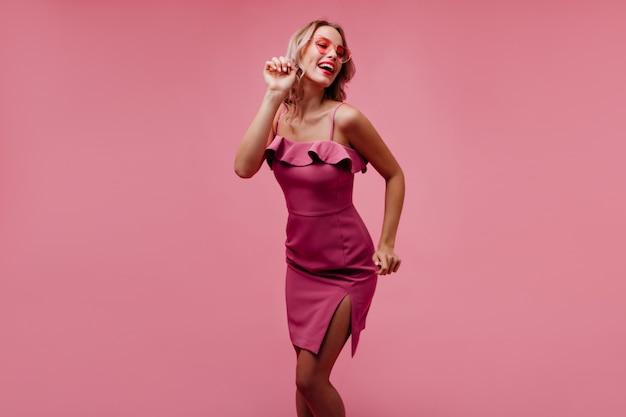 Frohe frau im eleganten rosa kleid, das mit lächeln tanzt