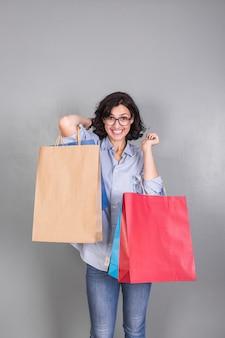 Frohe frau im hemd mit einkaufstaschen