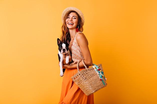 Frohe frau im sommerhut, der französische bulldogge hält. lachendes mädchen im orangefarbenen rock, der mit lustigem welpen aufwirft.