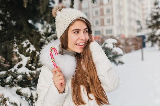 Frohe frau mit langen glänzenden haaren, die zuckerstange halten und wegschauen. foto im freien von gut aussehender blonder frau mit lutscher, der winterurlaub genießt ..