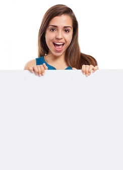 Frohe frau mit langen haaren und einem leeren plakat