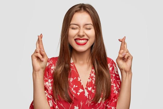 Frohe frau mit rotem lippenstift, der gegen die weiße wand aufwirft