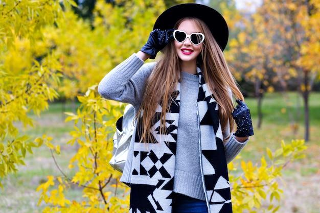 Frohe frau trägt eleganten mantel und schwarzen hut, der in sonnenbrillen am sonnigen herbsttag aufwirft. porträt im freien des begeisterten weiblichen modells im trendigen grauen pullover, der im park mit gelben bäumen geht.