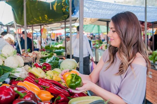 Frohe frau wählt grüne und rote paprika im supermarkt shoppin