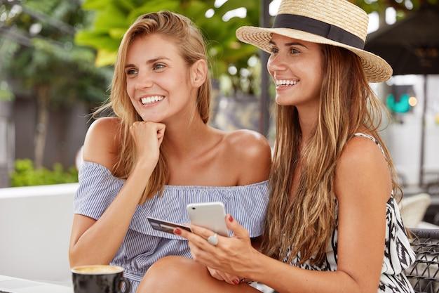 Frohe frauen, die sich freuen, einen gutaussehenden mann zu sehen, sitzen zusammen im terrassencafé. hübsche brünette frau in stilvollem sommerhut, hält kreditkarte und smartphone, verwendet mobile anwendung für online-kauf