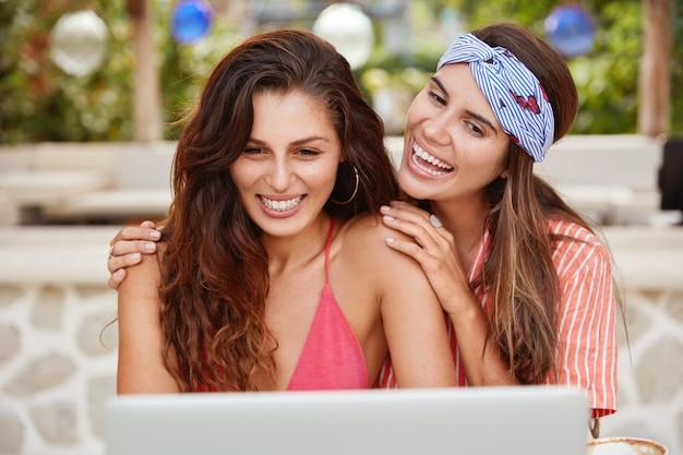 Frohe frauen umarmen und posieren vor der kamera eines laptops, tätigen videoanrufe und sprechen mit freunden, teilen impessionen, um im ausland urlaub im tropischen land zu machen.